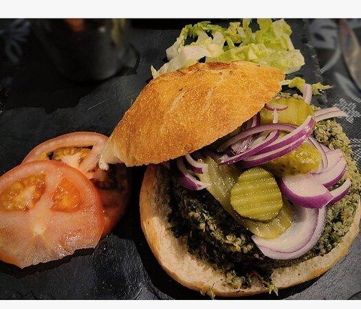 Hamburguesa vegana de quinoa y espinacas. Elaborada con quinoa, espinacas, ajo, pimentón dulce, pimiento rojo, sal pimienta, pan rallado y acompañada de lechiga, tomate, cebolla morada y pepinillo.