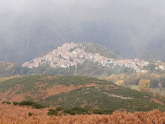 Montefegatesi, إيطاليا: In una pausa della nebbia appare la vista del paese di Montefegatesi dalla vetta del Monte Coronato