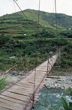 """الفلبين: Il ponte che, dalla """"strada"""" che congiunge Bontoc a Tabuk, permette di passare da un lato all'altro della valle del Chico superando il fiume omonimo che si vede in basso. Ponte di accesso a Bugnay e all'imbocco del quale c'è il guardiano la cui foto è stata prima pubblicata.  Isola di Luzon - Filippine.  Diapositiva digitalizzata.  Cliccare sulla foto per vederla come scattata."""