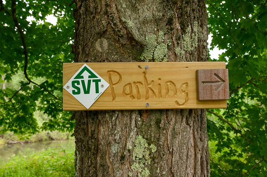Sign with SVT blaze and arrow indicating where the parking lot is at the Fairground Trailhead.