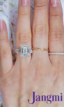 6ct Emerald cut on our three stone baguette setting in platinum.