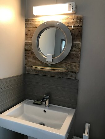 Room Four - stunning mirror, made by us, using an old industrial washing machine door, backed with driftwood. Book Direct for the BEST PRICES.