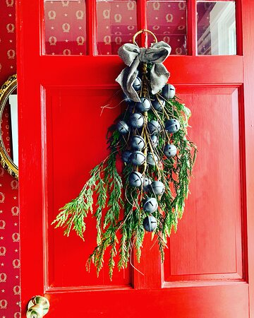 Front door with Christmas bells and fresh greenery