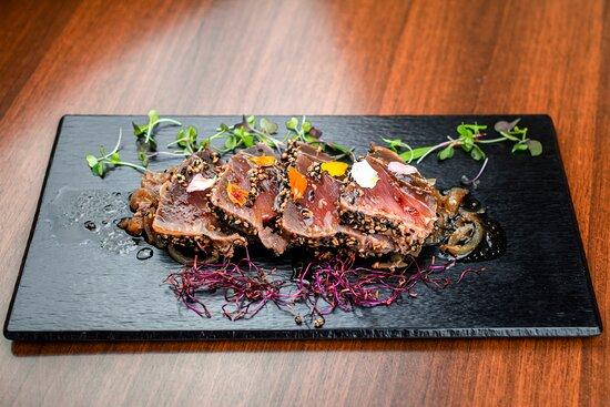 Tataky de atún tibio marinado con vinagreta de soja y cebolla caramelizada.