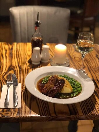 Sausage and mash served with onion gravy and peas