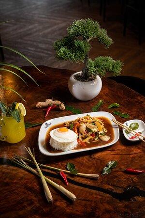 GAI PHAD GRA PRAU SPEZIAL Gehacktes Hühnerfleisch mit Bohnen, Paprika, Peperoni, Zwiebeln, Bambussprossen, Thai-Basilikum, Spiegelei und Reis