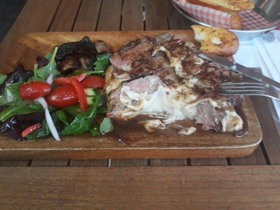 Skirt steak on mash potato with mushrooms and salad.