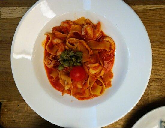 Паппардели с креветками, кальмарами, помидором черри, каперсами (в меню указано, что они с маслинами, но судя по всему маслины заменили каперсами) и чесноком в томатном соусе.