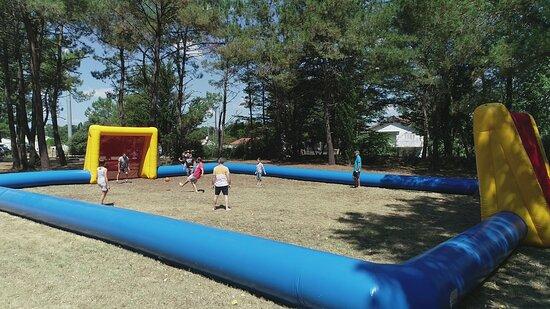 Structure de jeux gonflable avec à proximité terrain de volley, badminton et pétanque