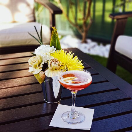 """Enjoy one of our hand crafted cocktails in our lounge seating on the patio. Pictured here is """"Sunkissed""""; a gin cocktail using our very own Warner's Raspberry Gin."""