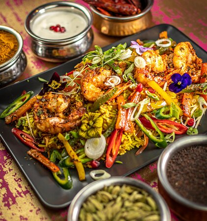 King Prawn - Inspired by the royal court of the Mughal Empire. Rich in nutrition, the buttery, spiced vegetable rice is oven cooked and served with raita.