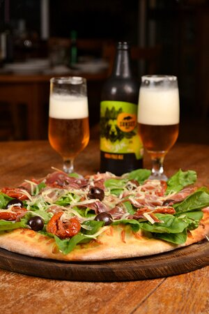 Pizza sabor Rúcula acompanhada de cerveja especial.