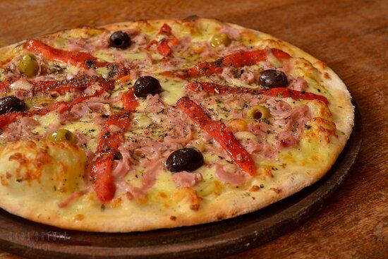 Pizza assada no forno a lenha sabor Argenta. Ingredientes: molho de tomate italiano, mussarela, presunto, pimentão assado, azeitonas e orégano.
