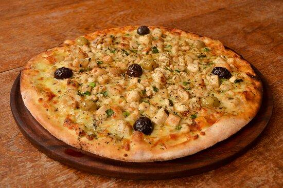 Pizza assada no forno a lenha sabor Frango ao Verdeo. Ingredientes: Molho de tomate italiano, mussarela, frango ao wok com cebolinha, azeitonas e orégano.