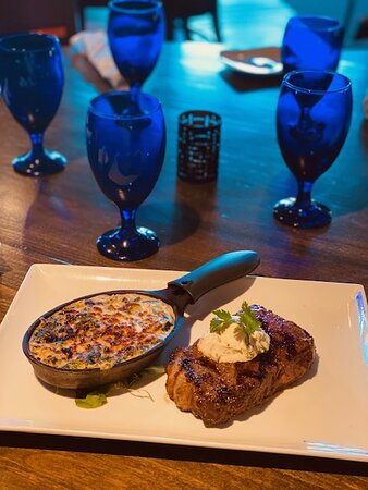 Dinner menu item- Carne a la Brasas.  12 oz. New York strip steak, cooked to temperature topped with Jalapeno Herb butter with creamed spinach.