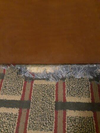 Damaged rug in room.