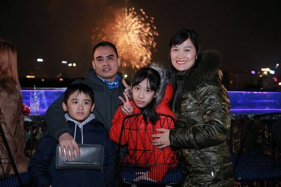 A family at NY's Eve - Firework from Hoan Kiem Lake at the background