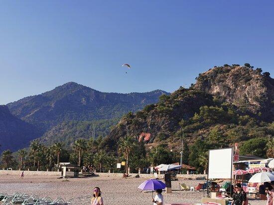 "Параплайнерист над пляжем, вид в сторону ""Голубой лагуны"". Paraglider over the beach, view towards the ""Blue Lagoon""."