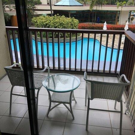 Varanda com vista para piscina com cadeiras confortáveis .