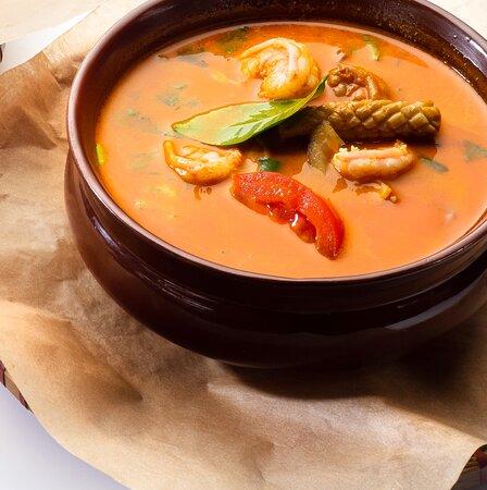 Том Ям – кисло-остро суп с морепродуктами  Состав: кальмар, креветка, куриный бульон, рыбный соус, паста, чили, лемонграсс, сок лайма, кинза, сельдерей, белый лук, шампиньоны, кокосовое молоко, ананас, помидор, паровой рис.