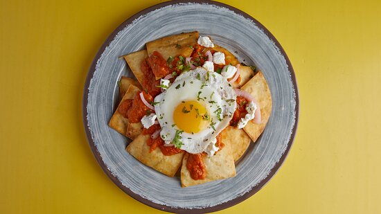 Chilaquiles Αυγό μάτι με ανθότυρο και avocado πάνω σε τηγανητές πίτες αλευριού με ranchero sauce, κρεμμύδι πικλα, κόλιανδρο και φρέσκο lime.
