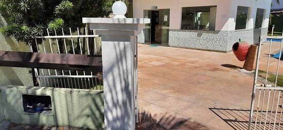Entrada do hotel com hidrometro desativado. Vista para a recepção e piscinas a direita.