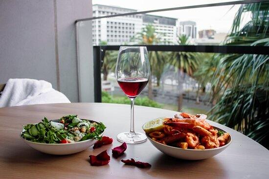 Green salad and seafood-based pasta dinner (and red wine) option available from the hotels bar & Grill - can be enjoyed from the sundeck, grill, or from the luxury of suite balconies.
