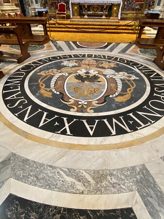 The floor design is centred on a large tondo containing the heraldry of Pope Paul in pietra dura.