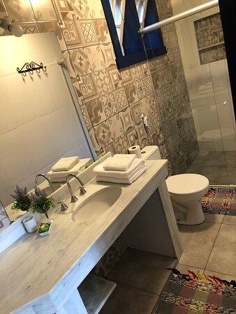 banheiros amplos e modernos com bancada e água quente na pia)