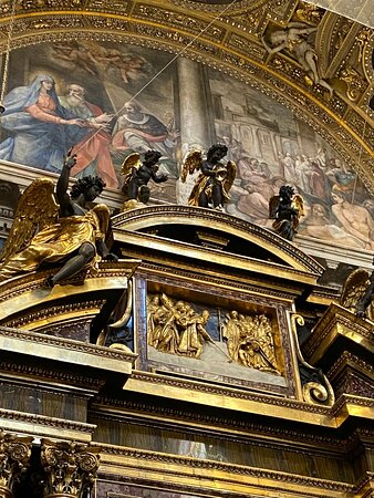 It has two pairs of gigantic ribbed Composite columns in red marble with gilded ribs, supporting the halves of a split segmental pediment, on which sit two angels executed by Guillaume Berthelot from a design by Camillo Mariani.