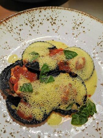 Ravioli al nero di seppia ripieni di polenta con moscardini e pomodoro