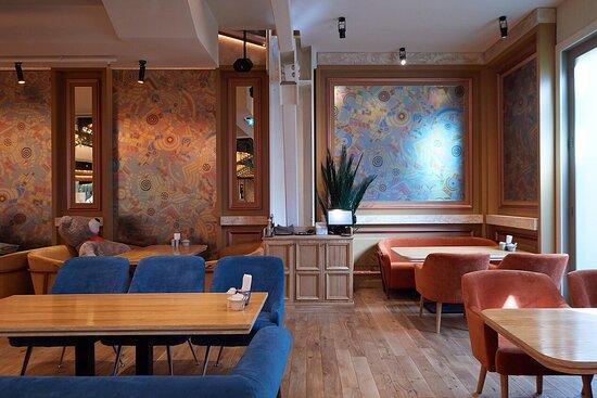 Внутри нас ждёт большой просторный зал с пальмами, велюровыми диванчиками и креслами в стиле ретро.