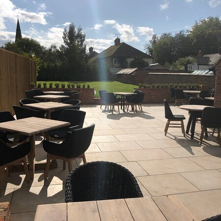 A beautiful outside dining area with a large enclosed lawn