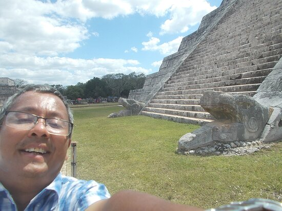 """Near the bottom of the El Castillo's north stairway (with a """"serpent sculpture"""" on each side of the stairway which is the """"only such"""" stairway among the 4 stairways of the Pyramid)"""