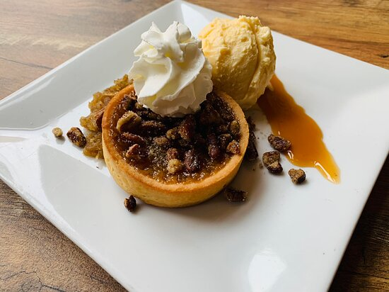 With apple preserve, spiced pecans, caramel, ice cream, and whipped cream.