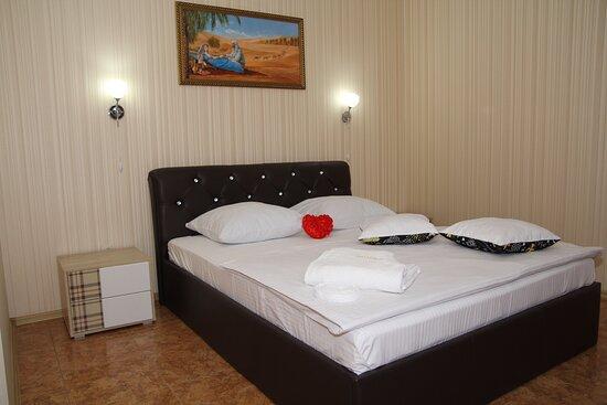 """Volgodonsk, Russia: Номер """"Люкс"""" - номер разделен на 2 зоны, в спокойных пастельных тонах с идеально составленным интерьером. Разделение на две комнаты зонирует пространство на спальню и маленькую гостиную. Спальня оборудована удобной двуспальной кроватью, гостиная - современным диваном. Площадь - 37м2. В номере: балкон, двуспальная кровать 1600x2000, шкаф бельевой, холодильник, буфет для посуды, диван, телевизор 40"""", журнальный стол, ванная комната с душевой кабинкой, средства для гигиены, халат, полотенца 3 шт."""