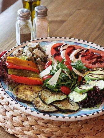 Notre ANTIPASTI : Tranches aubergines, poivrons et corgettes grillés, roquette, tomates cerises, tomate fraîche, mozzarella fleur de lait, parmesan & sauce mozza