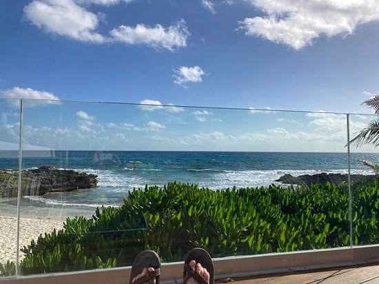 sitting at the end of the pool deck, looking at the beach and cove