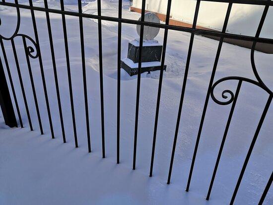 За оградой в снегу утопает какое-то надгробие...