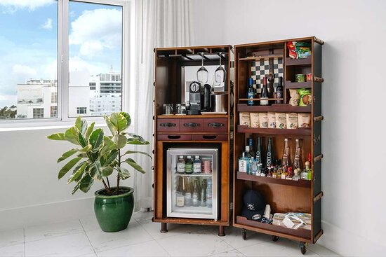 Vintage chests open to reveal mini bars stocked with a well curated collection of drinks, snacks and treats.