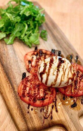Burrata & Italian Balsamic Glaze - Fresh burrata cheese, arugula, fresh tomatoes, Italian balsamic glaze served with thin crispy Focaccia