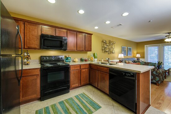Fully equipped kitchen with bar-stool seating open to living room