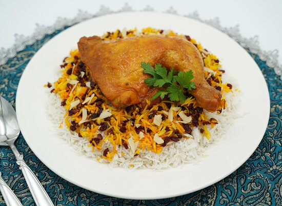 ZERESHK POLO Chicken cooked in a tomato saffron sauce. Served with saffron rice, sliced almonds and barberry.