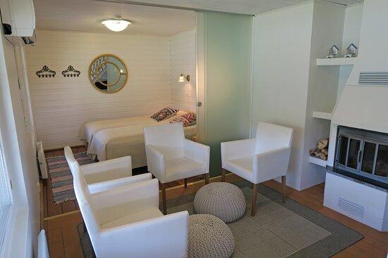 Villa Ozero, vietä rentouttava loma Tahkon keskustassa, Alakerrassa on takkahuone ja lasiseinällä erotettava makuuhuone.