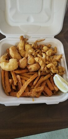 Combo seafood platter featuring our clam strips, shrimp and sea scallops shown here with sweet potato fries