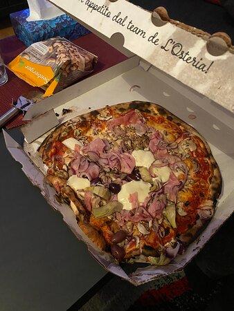 Pizza liegt teilweise zermatscht auf der einen Hälfte des Kartons.