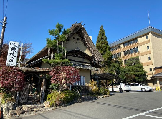 Quaint Staw-roofed cottage marks the Entrance to Ryokan Nenrinbo. The Parking Lot, then New Building on right.