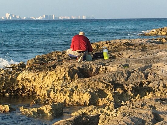 Fishing in front of Cancun Club Med packing his fish.