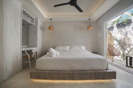 Habitación con balcón  hacia una vista espectacular a nuestro mural Layla y piscina, acomodada con con una cama King, A/C, Smart TV, ventilador, closet, caja de seguridad y baño privado.