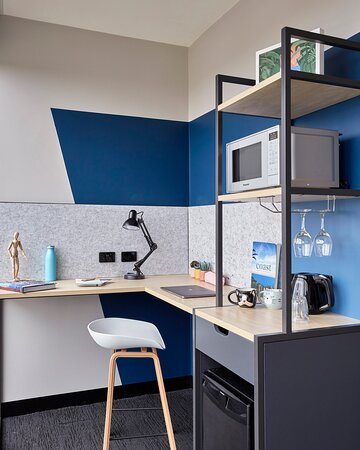 Greater Queen- or Double-bedded Room Desk in L-shape with pantry featuring a microwave, bar fridge, and kettle. The desk is equipped with multi power sockets.